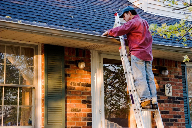 A homeowner stands on a ladder to clean out his gutters