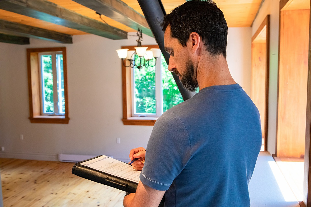 A contractor with a clipboard standing in an empty living room