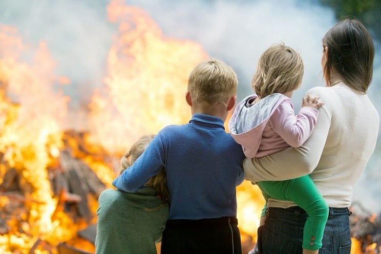 A family huddles outside of their home, which is in flames