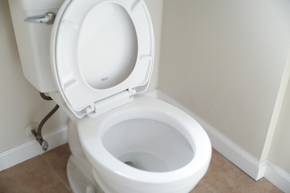 A toilet in a small bathroom has its seat raised