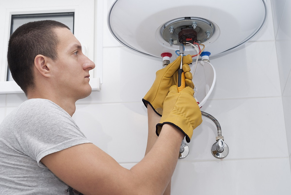 A qualified professional inspects a hot water heater.