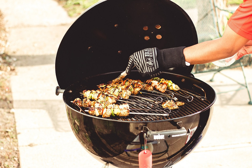 A person wearing fire-resistant gloves adds sauce to chicken on a charcoal grill