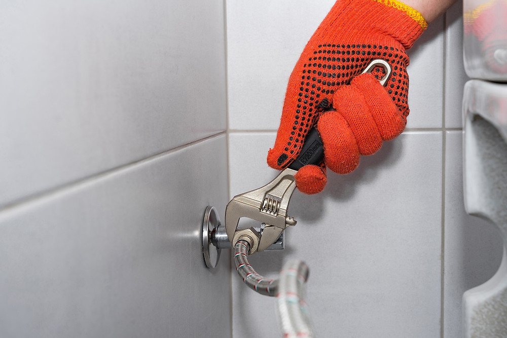 A homeowner in gloves tightens a braided metal hose on a toilet with a wrench