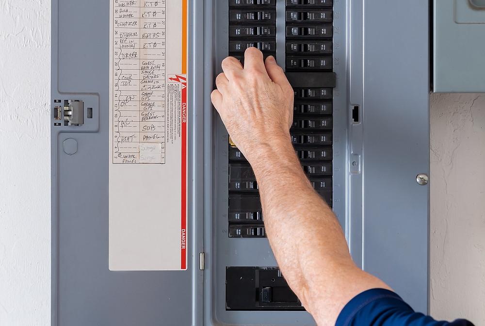 A homeowner flips a circuit breaker in the breaker box