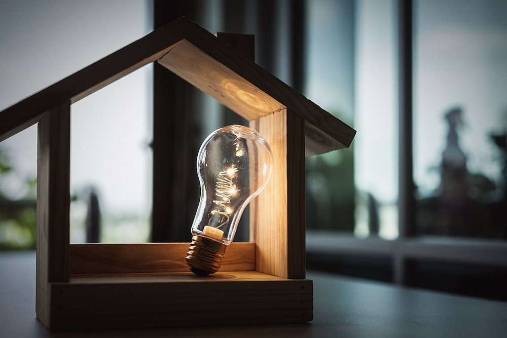 A light bulb is illuminated in a tiny wooden home