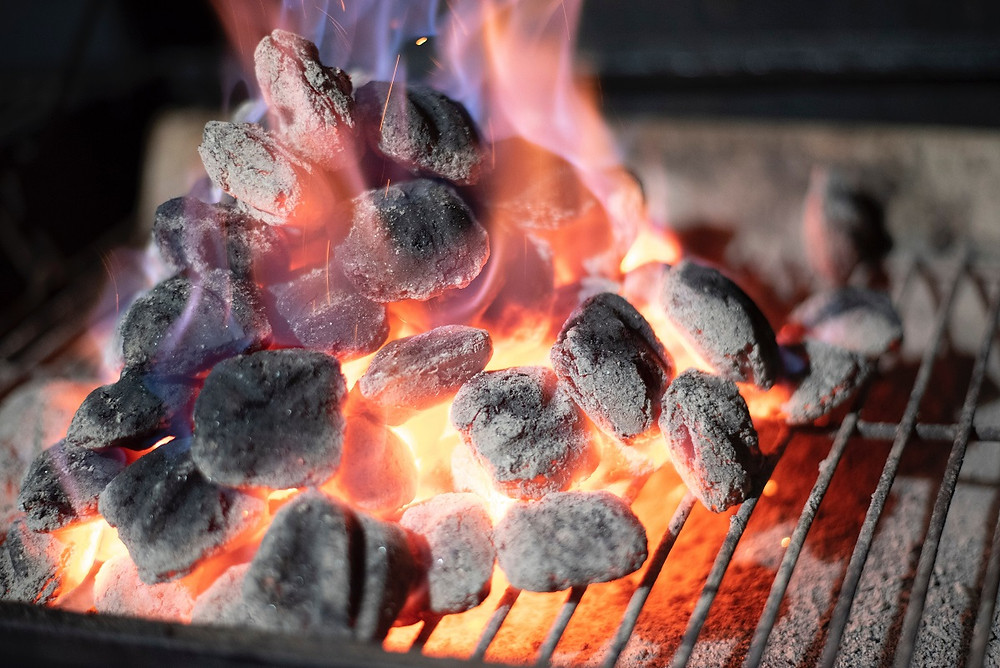Coals are starting to turn white as they lay aflame on a grill