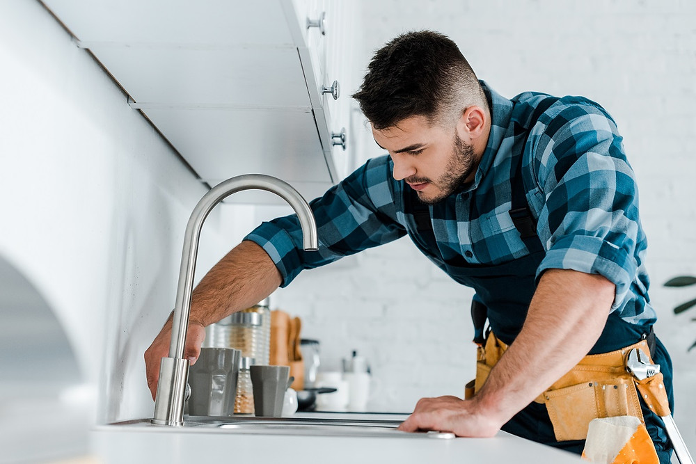 A plumber inspects a kitchen sink faucet