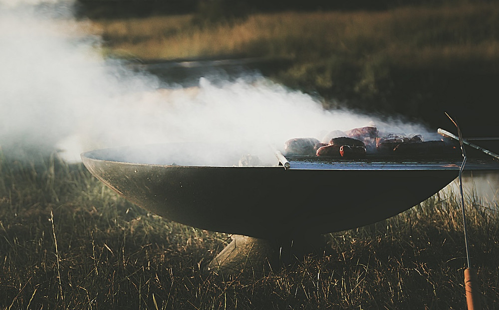 Smoke rises from a grill that still has steak on it.