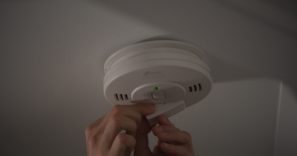A homeowner changes the battery in a smoke detector