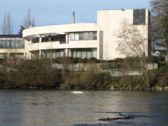 Picture of a large concrete building overlooking a river bank.