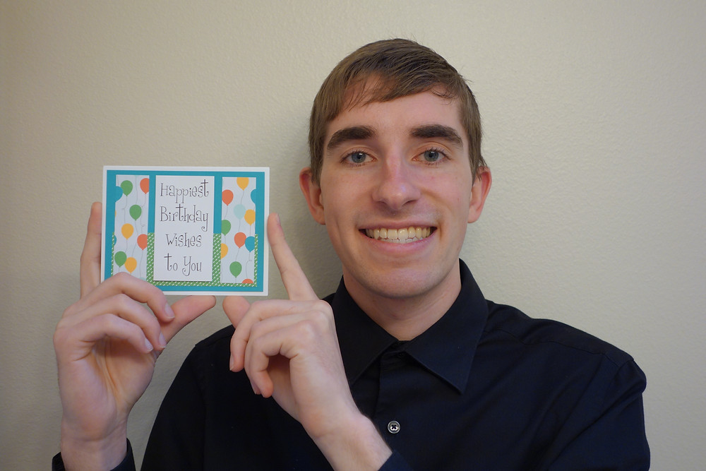 A photo of Kent holding a hand-made birthday card
