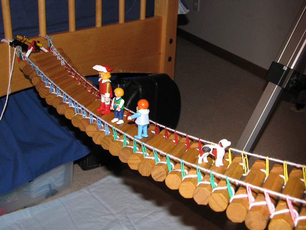 Photo of a toy suspension bridge built with continuous yarn holding up a Lincoln Log deck with paperclips