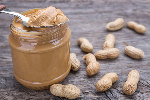 Spoon scooping creamy peanut butter out of a glass jar, with raw peanuts strewn around
