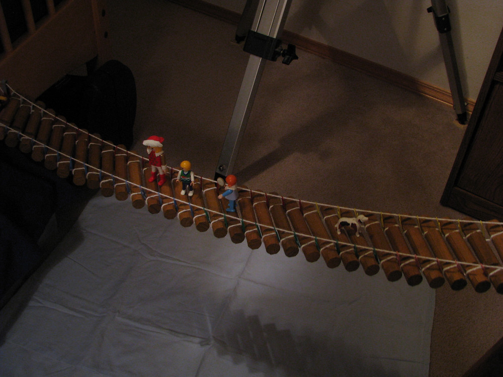 Another photo of toy figures standing on the Lincoln Log/paperclip/yarn bridge