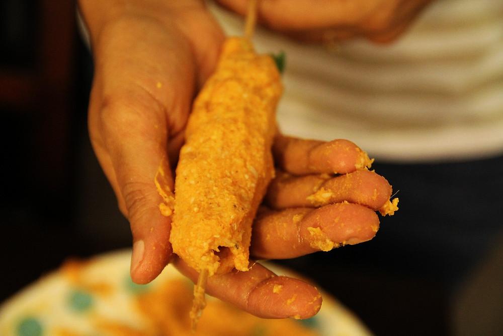 Image of kebab being pressed on a skewer
