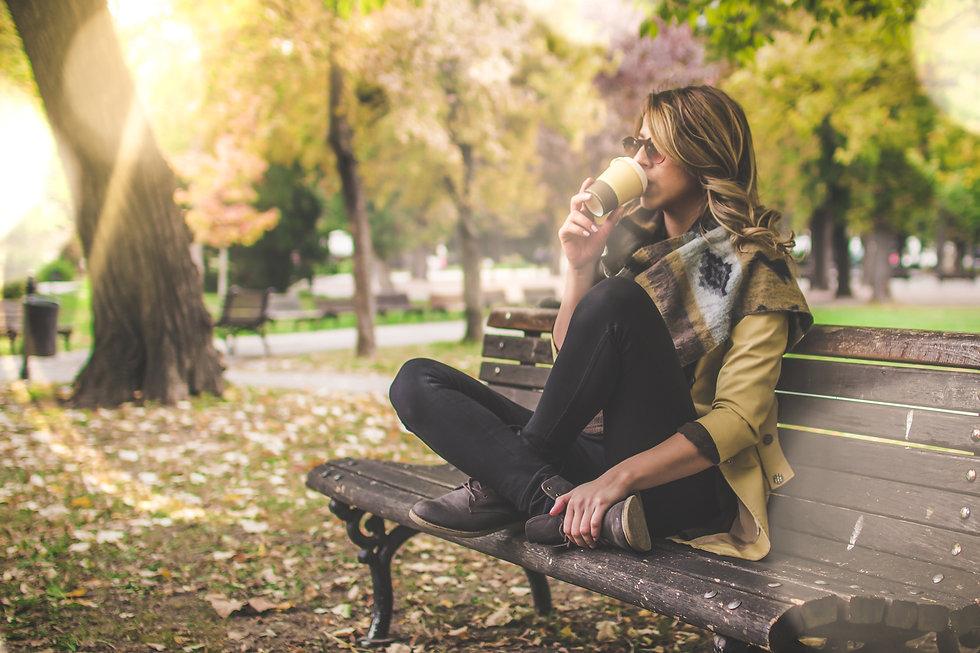 Happy woman drinking coffee in park.jpg