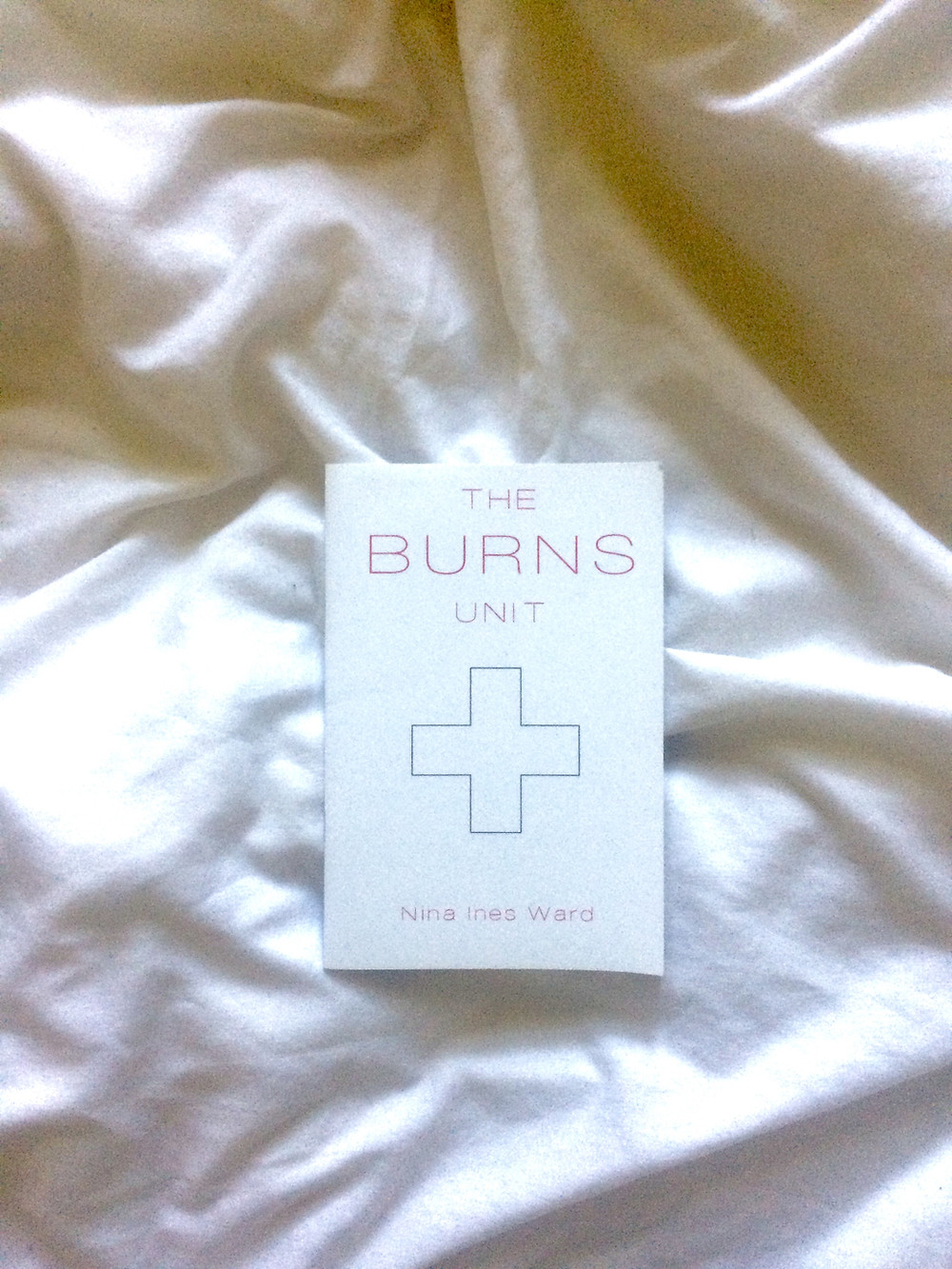 Photo of the pamphlet 'The Burns Unit' by Nick Ines Ward on a white crumpled duvet cover, with natural light shining over. The pamphlet is white with pink writing and the outline of a cross in the centre.