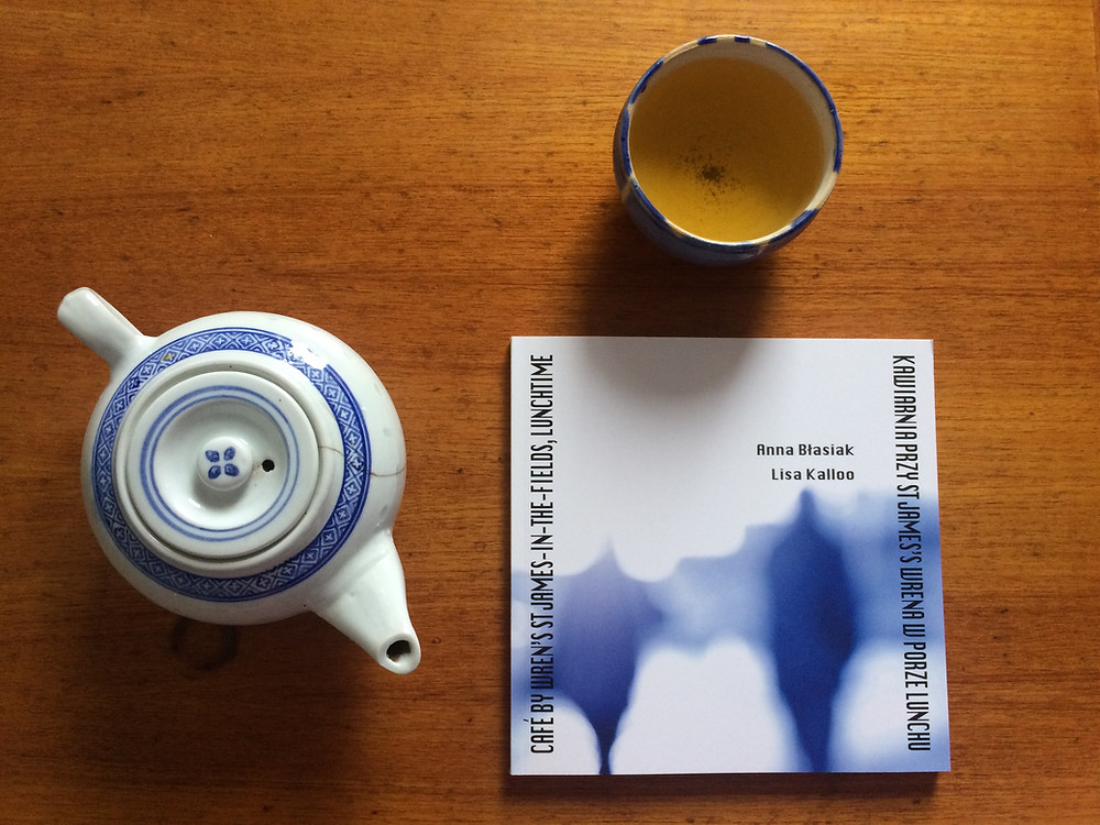 Book with blue silhoeuttes on white background, presented on wooden table with teapot