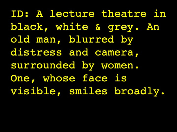 Image Description: A lecture theatre in black, white & grey. An old man, blurred by distress and camera, surrounded by women. One, whose face is visible, smiles broadly.