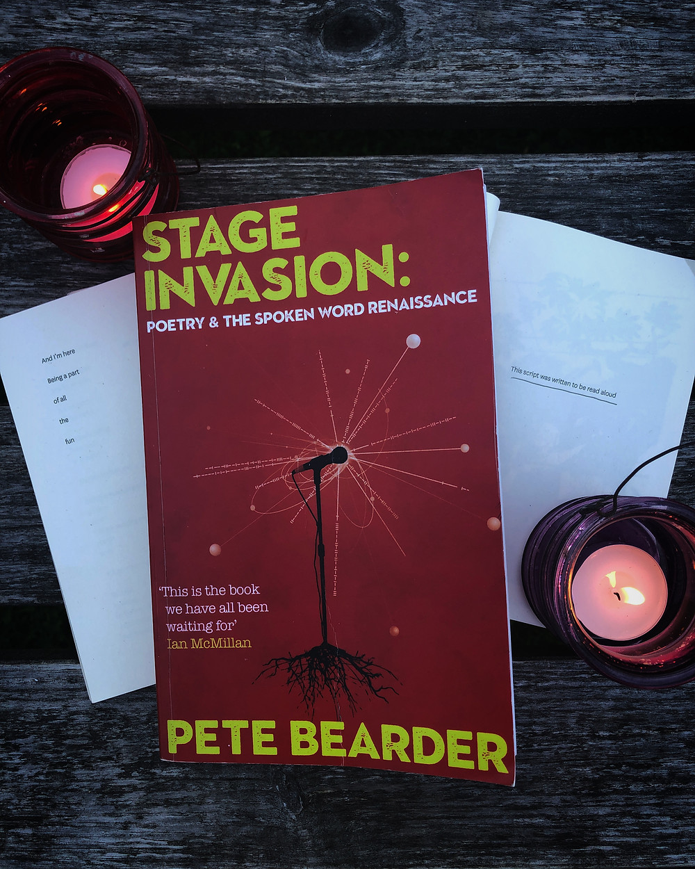 Stage Invasion book cover next to two tealight candles