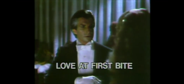 a man in a tux stares with frowning expression; text reads 'LOVE AT FIRST BITE'