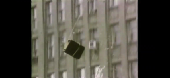 Some kind of armchair or box is thrown from a high-storey window