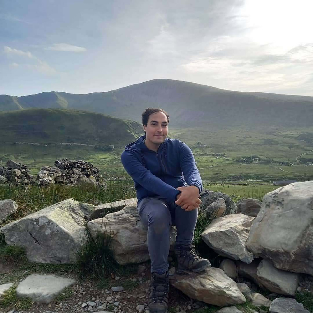 Mau is smiling at the camera and wearing a blue hoodie and sitting on some rocks with beautiful rolling hills and dry stone walls, blue sky in the background