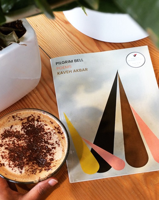 Photo of a copy of Pilgrim Bell: Poems, by Kaveh Akbar. The front cover is light grey, with jets of different colours overlapping: yellow, pink, black and brown. The collections sits on a wooden coffee table with a cappuccino held.