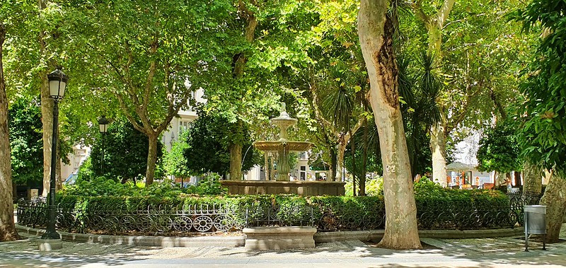 Lanscape photo of Plaza de Trinidad, Granada, with a stone fontain in the centre in sunlight surrounded by lush green trees and a circular fence design. In the foreground you can see a pavement and black lampshades surroundinmg the fountain. In the background, some white buildings can be seen peeking through the trees.