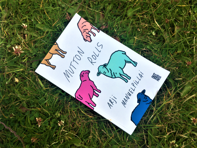 Copy of 'Mutton Rolls' by Arji Manuelpillai (Outspoken Press, 2020) on grass. The cover conveys illustrated sheep in bright colours (pink, green, blue, yellow) on a white background.