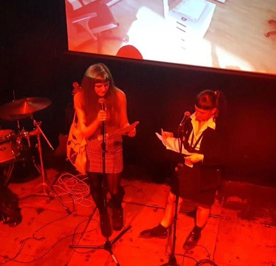 editors Maria Sledmere & Denise Bonetti at the launch of issue #5, Notes from the Watercooler (The Poetry Club, 2017) - standing onstage reading from paper among red light