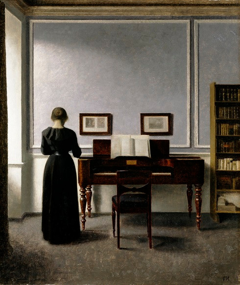 Young woman seen from behind in grey interior with piano/harpsichord and a bookshelf, chair, two paintings with details unseen