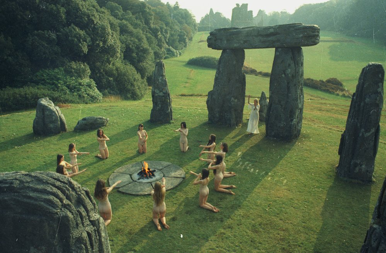 naked woman among standing stones kneel around an altar