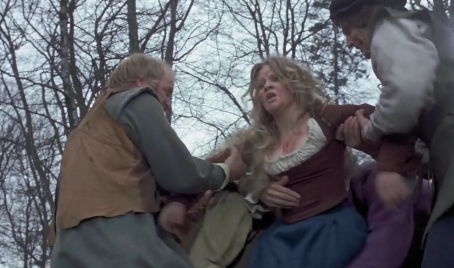 a woman in distress with blood on chest handled by two men against skeletal trees