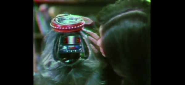 Long haired person tenderly touches the face of crowned robot apparently wearing a wig