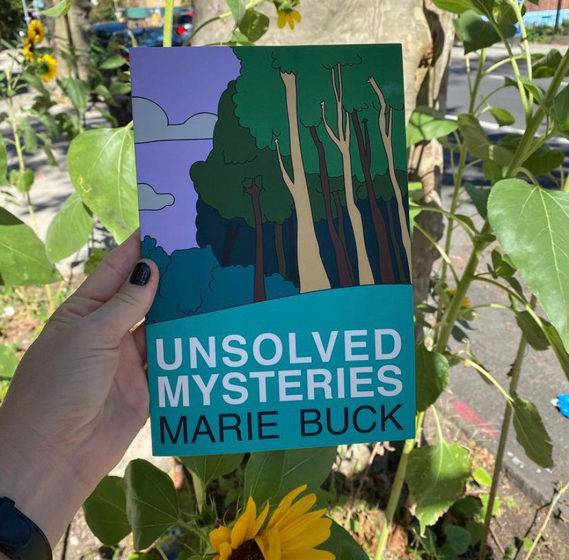 A hand with black nail polish holds up a copy of Unsolved Mysteries (cartoon style trees on the cover with teal beneath black and white text) with sunflowers in the background.