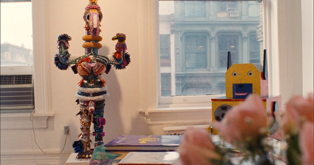 Video still taken from Mubi of 'All the Vemeers in New York' (1990): a close up of a windowsill looking out on a opposite building, presumaly in a city during the day. The walls are white. A table is in the forefront on which stands a multi-coloured object of a creature with arms and hands oustretched with the hands in the shape of birds. Eyes can faintly be made out on the top of the body, standing upright like a human. Beside it lies a purple book and beside that a yellow box with a cardboard yellow cut out of a robot like face with blue sticking up ears attached. In the foreground, very blurred, we can make out pale pink roses.