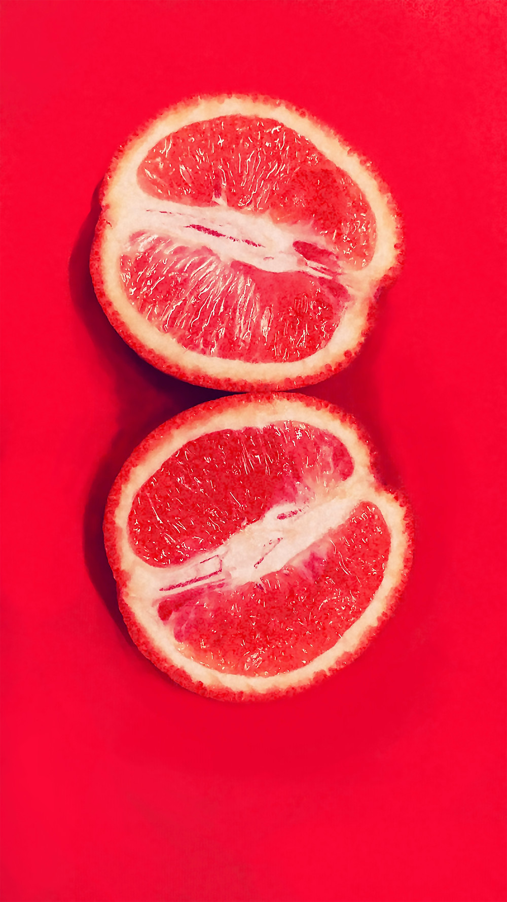 Two halves of a pint grapefruit on a red background.