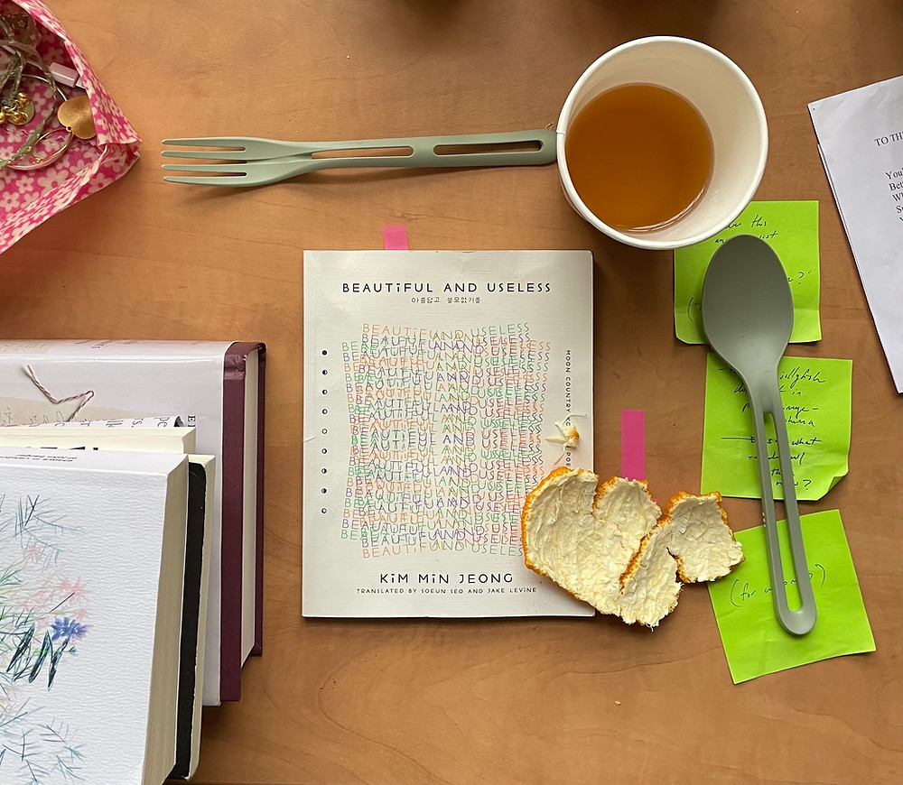 Beautiful and Useless sits on a wooden surface alongside cutlery, acid green sticky notes, orange peel, a half-drunk cup of tea and other books.