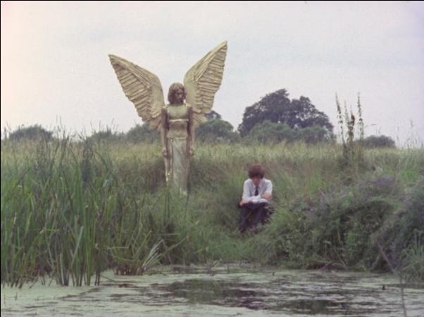 golden angel looks down at person kneeling by algae-coated river looking downwards/ahead