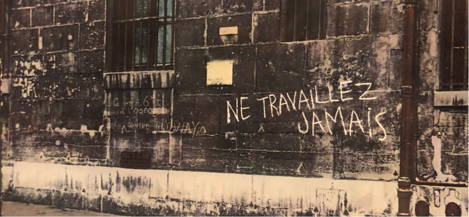 Sepia toned photo of a wall with phrase 'Ne travaillez jamais' in capital letters, written in white chalk.