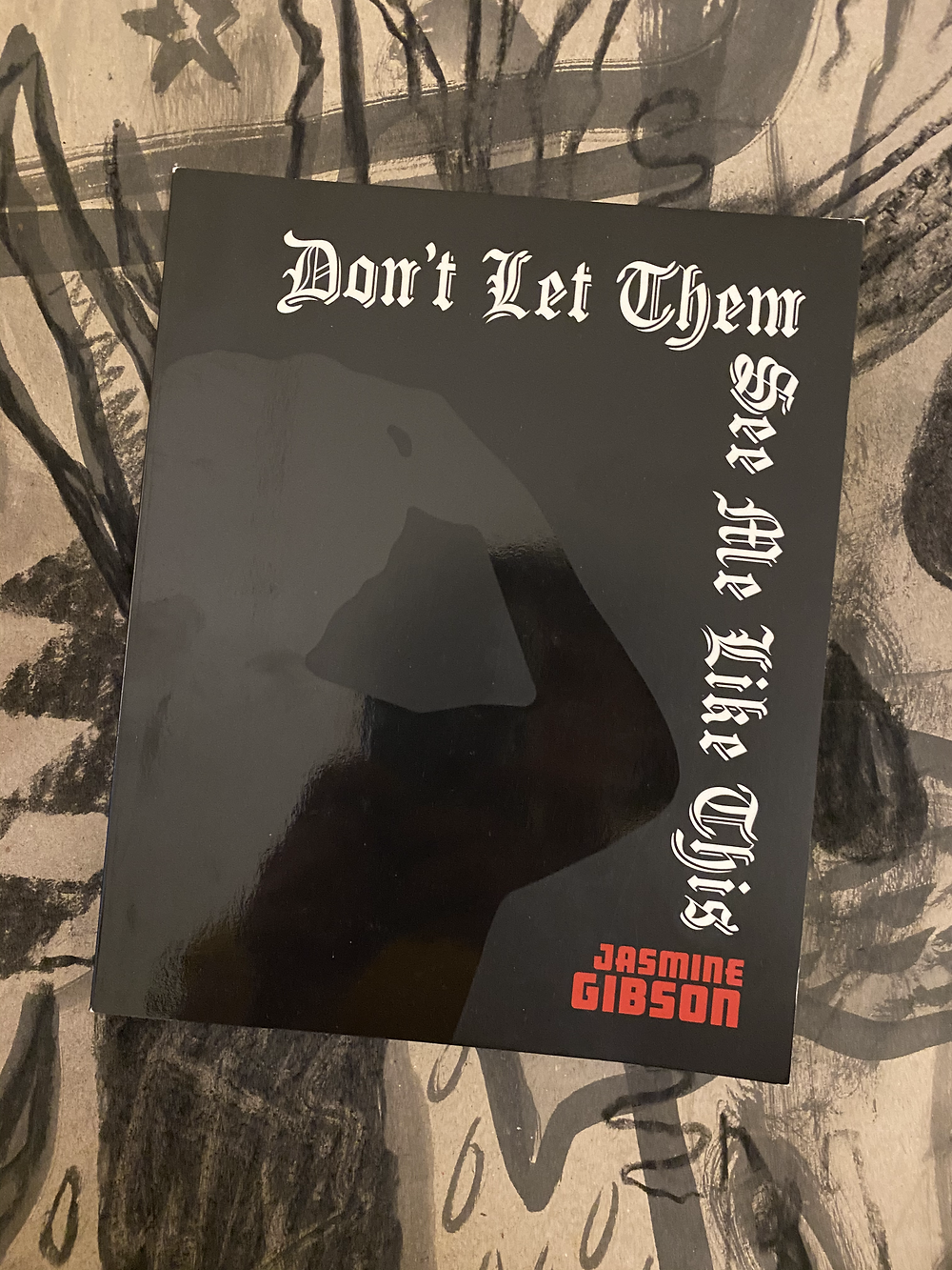 The cover for Gibson's book Don't Let Them See Me Like This is presented upon a charcoal drawing on cardboard backdrop