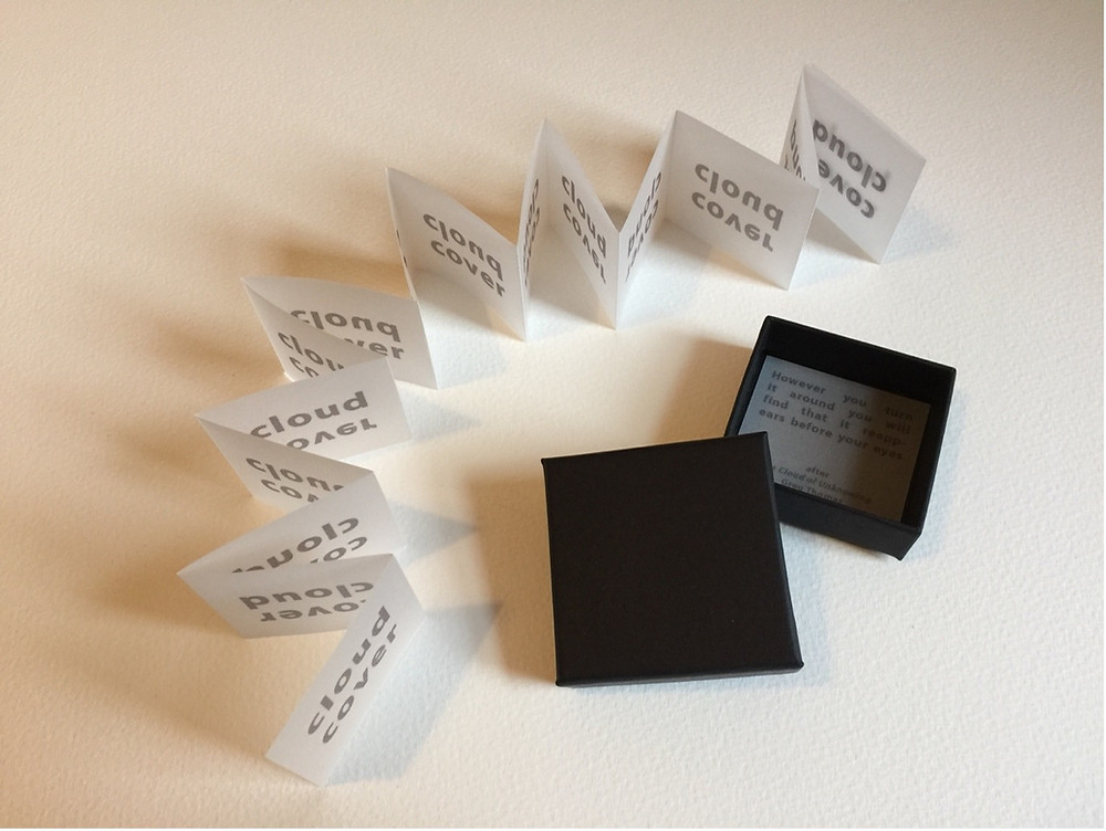 A tracing paper concertina stretches around a black jewellery-style box with another piece of paper in it