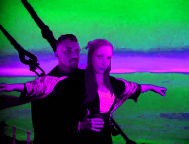 The 'Jack I'm Flying' scene from Titanic is shown with Verity up front in acid green and purple colours