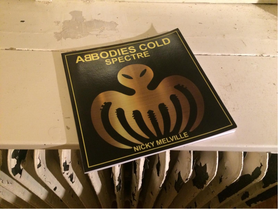 Copy of ABBODIES COLD: SPECTRE by nicky melville on a white surface over a chipped white radiator. The book is large, square with a black background and gold capitalised lettering and a gold octopus outline