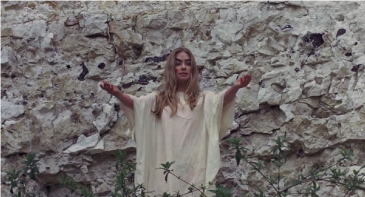 woman in white gown with arms raised against stone wall