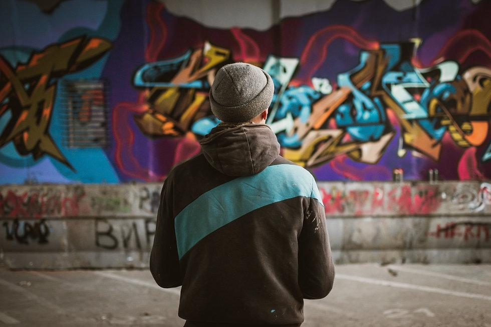 Graffiti artist standing near the wall.j