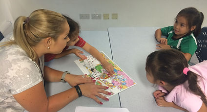 teacher with students actively engaged around a table in a classroom