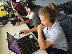 school kids sitting behind computers