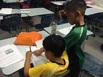 2 students working in their books in the classroom